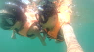 Couple snorkeling surface level in sea video