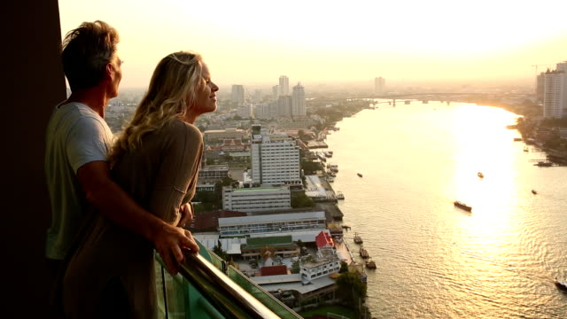 Couple stand on hi-rise deck, looks out across city, river video