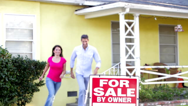 Couple Standing By For Sale Sign Outside Home video