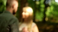 CLOSE UP DOLLY SHOT DEFOCUS Couple standing in forest on sunny day video