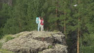 Couple Standing on Boulder Looking at Drone video