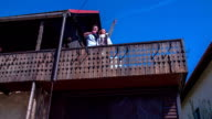 Couple standing on the balcony at the wooden vintage house and looking at the view over the countryside . video