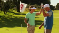 Couple standing on the putting green high fiving video