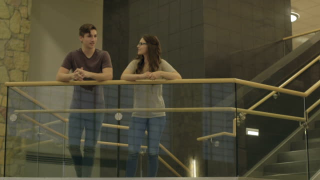 Couple Stands and Talks on a Stairwell video