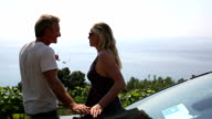 Couple step out of car, looks out to sea and hillside video