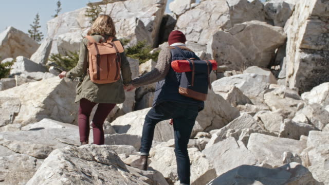 Couple Stepping Carefully on Rocks during Hiking Trip video