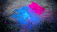 Couple stomping foot on colored powder on the ground video