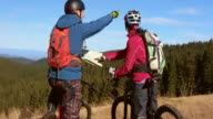 Couple stopping with bikes discussing right trail on map video