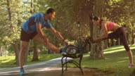 SLO MO DS Couple stretching on a park bench video
