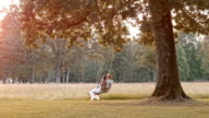 SLO MO TD Couple swinging under a tree at sunset video
