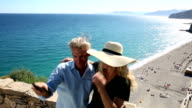 Couple take selfie pic on stone wall above beach video
