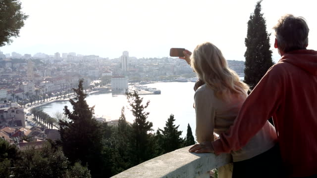 Couple take smart phone pic from viewing platform, above city video