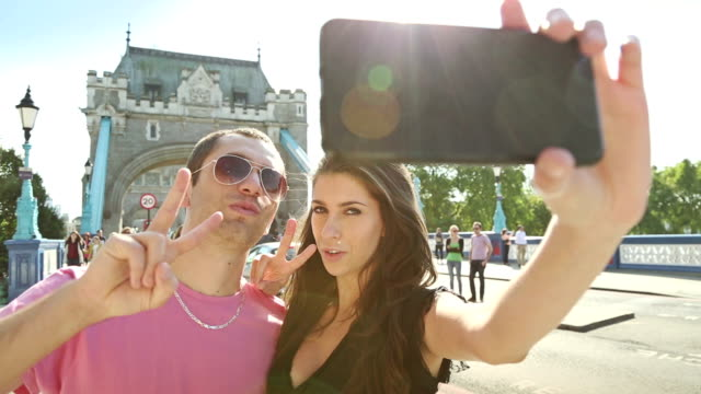 Couple takes a selfie in front of the Tower Bridge video