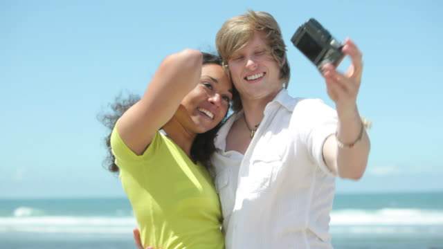 Couple taking photos at beach video