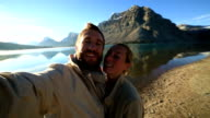 Couple taking selfie at sunrise by a lake video