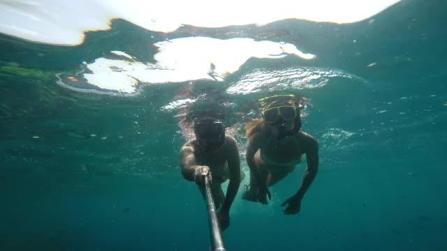 Couple taking selfies underwater video