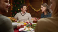 Couple talking at Christmas dinner and kids running around video