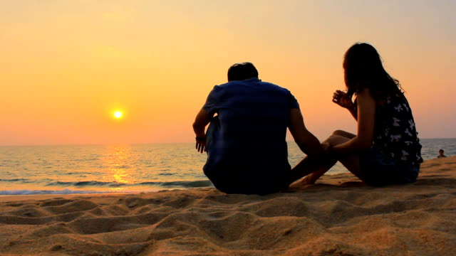 Couple talking at sunset beach video