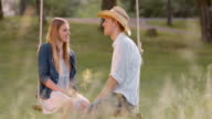 SLO MO DS Couple talking on a swing in nature video