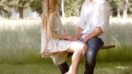 SLO MO TU Couple talking on a swing in the countryside video
