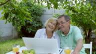 Couple talking through a laptop in the garden. video