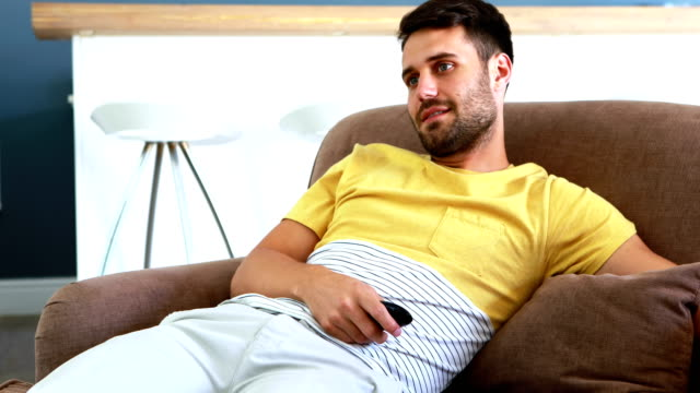 Couple talking while watching television in living room video