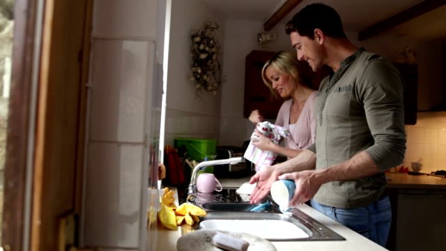 Couple talking whilst doing the dishes together video