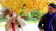 Couple Throwing Leaves In Autumn Garden video