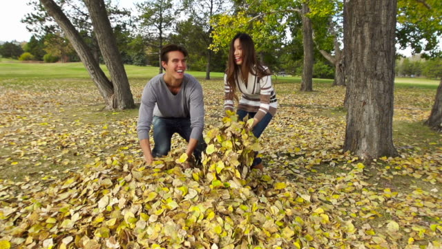 Couple throws leaves in the air during Autumn video