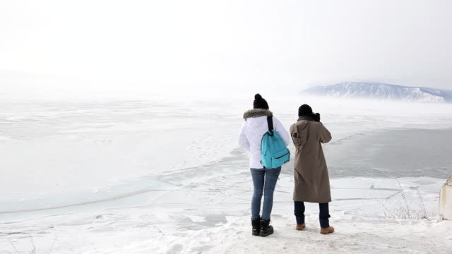 Couple travelers visiting lake with mountains in winter and take pictures video