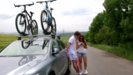 Couple traveling by car with bicycles on bike roof carrier video