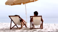Couple under parasol spending time together video