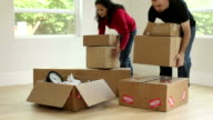 Couple unpacks boxes in new home video
