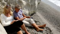 Couple use digital tablet in beach cove video