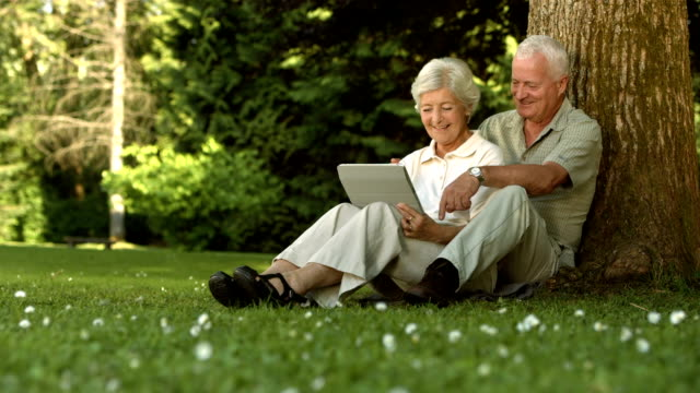 HD: Couple Using A Digital Tablet In The Park video