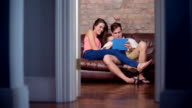 Couple using a digital tablet on a sofa video