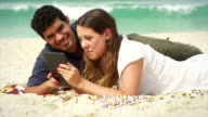 Couple using a tablet computer on a beach video