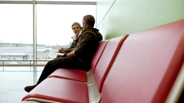 Couple waiting at airport terminal with tickets video