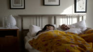 Couple waking up in bedroom video