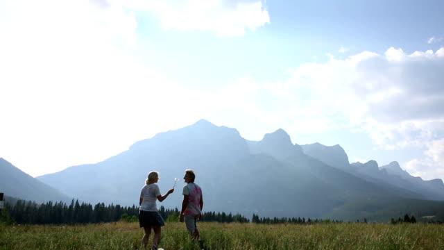 Couple walk across mountain meadow at sunrise video