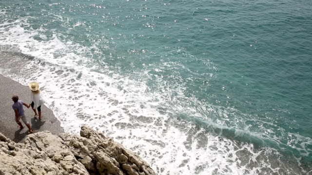 Couple walk along beach at edge of surf video