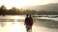 Couple walk along beach at sunrise, tidal flat video