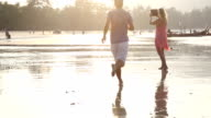 Couple walk along beach, take pic with digital tablet video