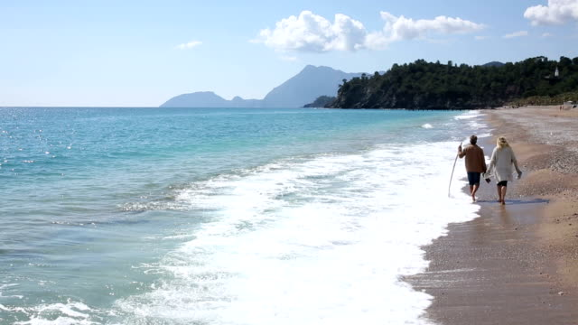 Couple walk along deserted beach by surf edge, mountains video