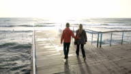 Couple walk along pier above sea, sunrise video