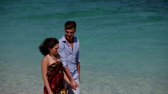 Couple walk together along the beach video