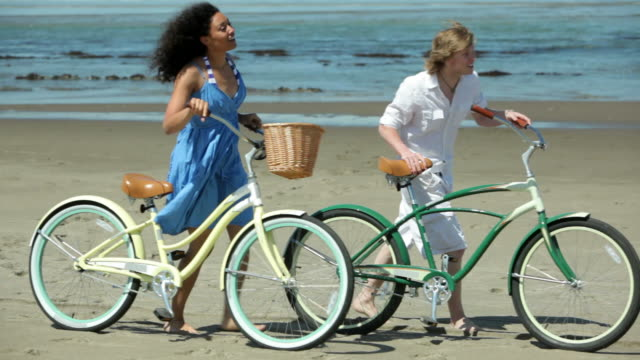 Couple walk with bicycles along coastline video
