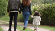 Couple walk with young daughter in a country lane, back view video