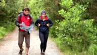 Couple walking along a country trail looking at map video
