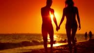 Couple Walking Along Summer Beach at Sunset video